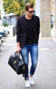 black blazer with black vest and blue jeans and white sneakers