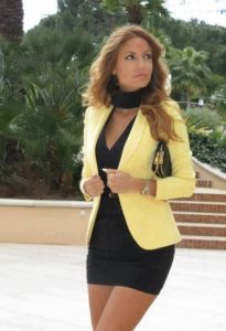 yellow blazer with short black gown and black neck scarf