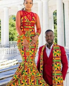 a kente fabric with dark red outfit the man rocked a plain red suit with kente muffler while the bride rocked a full kente gown - humourandstyle