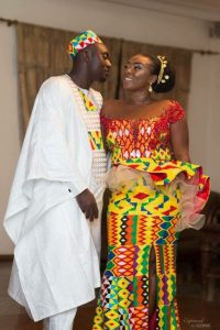 groom on plain agbada with kente cap matching the brides peplum dress - momoafrica