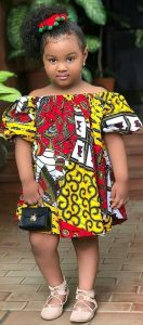 little girl posed on a short off shoulder ankara gown with a purse - latestfashion club