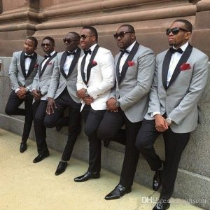 men on suit with groom at the center leaning on the wall with one leg up - amazepaperie