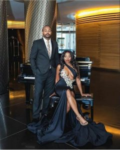 the lady sits like a queen in hot gown while the man stands like a body guard - nairaland